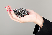 Woman in black business suit holds out a handfull of Jewels  Model released