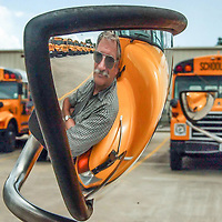 Friendswood ISD bus driver, Marshal Tate, is reflected in the mirror of one the new buses at the bus barn, 08/23/02.