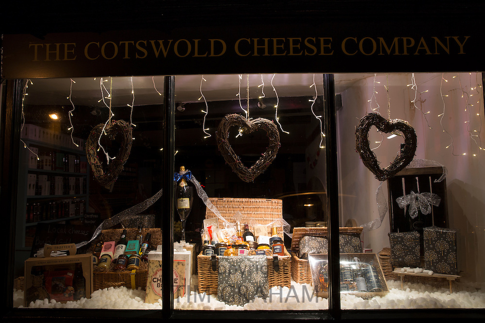 Window display of food shop with Christmas hampers on Burford High Street, The Cotswolds