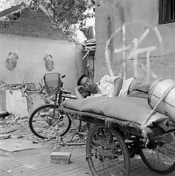 Man sleeping on tricycle next to a partially demolished house in a Beijing hutong