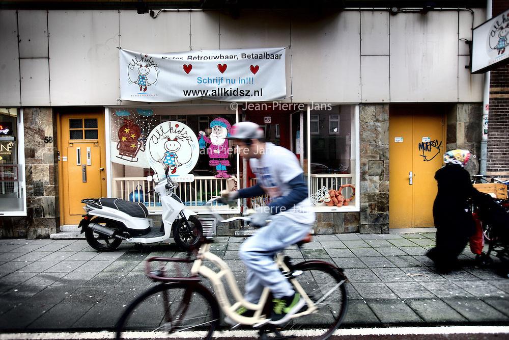 Nederland, Amsterdam , 27 december 2012..Kinderdagverblijf Allkidsz op de Admiraal de Ruijterweg maakt reclame door een spandoek aan de gevel te prikken met de woorden Beter, Betrouwbaar, Betaalbaar..Foto:Jean-Pierre Jans
