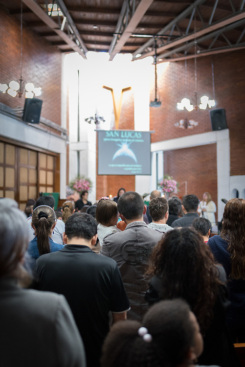 18 November 2018, Bogotá, Colombia: A father holds his daughter as they pray together during Sunday service in the Church of San Lucas. The church of San Lucas ('Saint Lucas') of the Evangelical Lutheran Church of Colombia, brings together a congregation of some 100 people in the southern areas of Bogotá. Located in the Kennedy area, the church has recently celebrated 50 years. As part of its ministry, the church runs a school and college, The Colegio Evangelico Luterano de Colombia (CELCO) San Lucas, offering education to just over 1,000 students aged 3-18. The school started as a social initiative offering care for children aged 0-4 in Bogotá's less wealthy neighbourhood, allowing the parents opportunities to go to work. 36 years after its foundation, the school employs 56 staff, of which 36 are teachers.