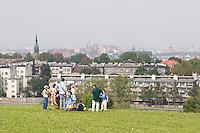School group sit admiring the view from the Krakus Mound in Podgorze Krakow Poland