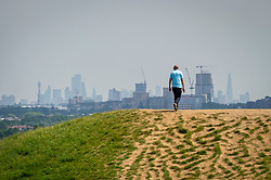 © Licensed to London News Pictures. 15/06/2021. LONDON, UK. The skyscrapers of the capital shimmer in the heat as a man walks at Northala Fields in west London where the temperature is expected to rise to 25C with a forecast warmer 29C tomorrow.  Photo credit: Stephen Chung/LNP