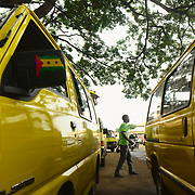 Shared taxis, that act as local buses, stopped in the center of São Tomé city.