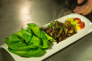 Turley lettuce wraps being handed to a server in the kitchen.