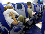 people trying to sleep during flight in commercial airplane economy class