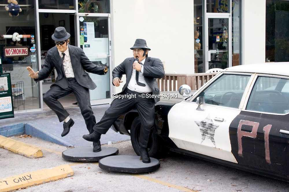 Jake and Elwood at the Blues Brothers Cafe singing and dancing beside police car.  Indian Rocks Beach Tampa Bay Area Florida USA