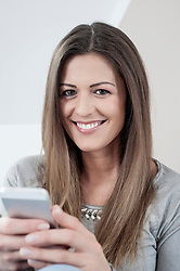 Portrait of smiling young woman with smartphone at home