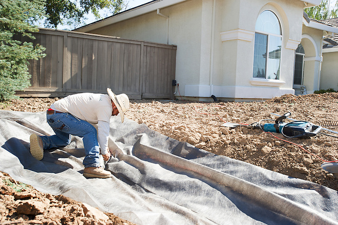 A couple from Roseville, Calif. a suburb of Sacramento, decided to take advantage of the Roseville Cash-for-Grass rebate program that pays 50 cents for every square foot of grass converted ($1000 maximum per single family) to a landscape with drought tolerant plants, mulch, ornamental rocks and dry streambed. A worker from Fallen Leaf Landscape of Rocklin, Calif. places landscape fabric on the area for a rock dry streambed. A series of 15 images is available for this project. Photo No. 8 was taken August 3, 2015. For details on the Calif. Department of Water Resources turf replacement program, visit www.SaveOurWaterRebates.com