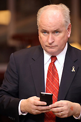 17 January 2015:  Illinois State Representative Dan Brady  checks his cell phone for messages during an NCAA MVC (Missouri Valley Conference men's basketball game between the Bradley Braves and the Illinois State Redbirds at Redbird Arena in Normal Illinois
