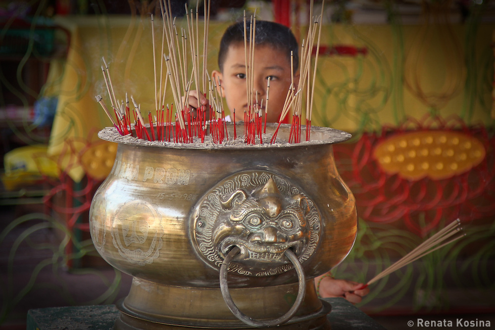 A young boy places his offering of burning incense sticks at Wat Chayamangkalaram, a Thai temple of The Reclining Buddha. The temple is located in Georgetown on the island of Penang, Malaysia.