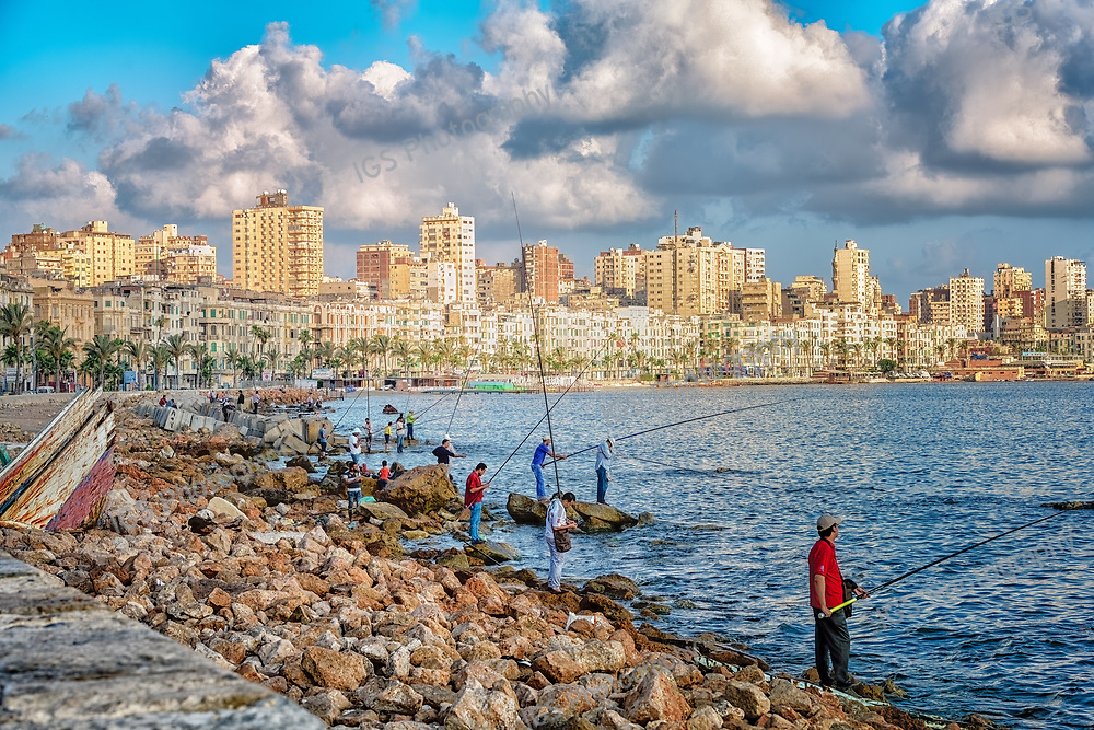 Fishermen on the rocky shoreline of Stanley Bay at sunrise, with the skyline of Alexandria in the background