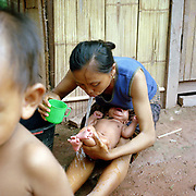A young Khmu mother washes her young baby in the traditional Khmu way by putting warm water in her mouth and 'spitting' it on the baby, Ban Chaleunsouk, Luang Namtha province, Lao PDR. The Khmu are the largest ethnic minority in Laos and belong to the Mon-Khmer sub-branch of the Austroasiatic ethnolinguistic family, who are considered the original inhabitants of Laos. One of the most ethnically diverse countries in Southeast Asia, Laos has 49 officially recognised ethnic groups although there are many more self-identified and sub groups. These groups are distinguished by their own customs, beliefs and rituals.