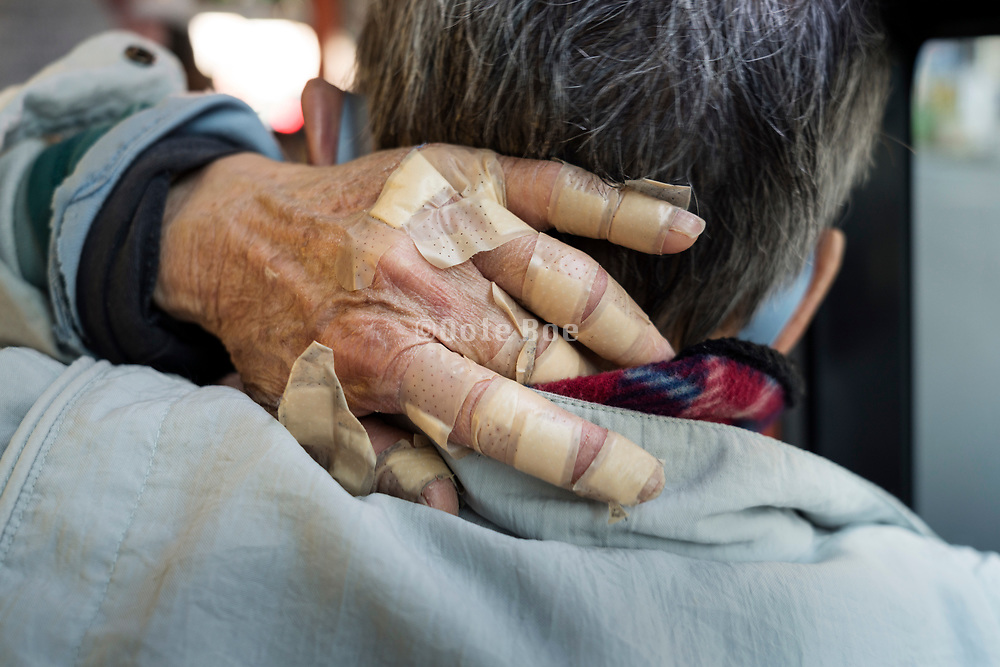 hand of a senior man covered with many plasters