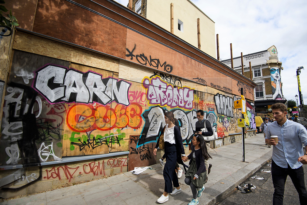 © Licensed to London News Pictures. 25/08/2018. London, UK. A business with it's windows boarded up on Portobello Road in Notting Hill, West London ahead of the 2018 Notting Hill Carnival which starts tomorrow (Sunday). Up to 1 million people are expected to attend this weekend's event that is one of the worlds largest street festivals. Photo credit: Ben Cawthra/LNP