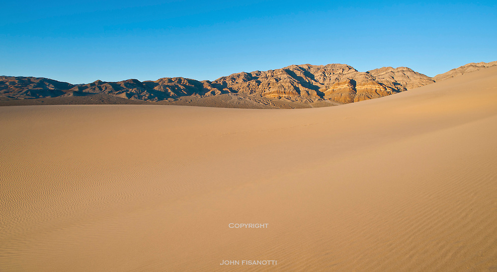 The Grapevine Mountains appear beyond the dunes just before sunset