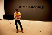 Man stands in front of a text artwork. I love Melancholy by Jeremy Deller at his show at the Hayward Gallery, London, UK.