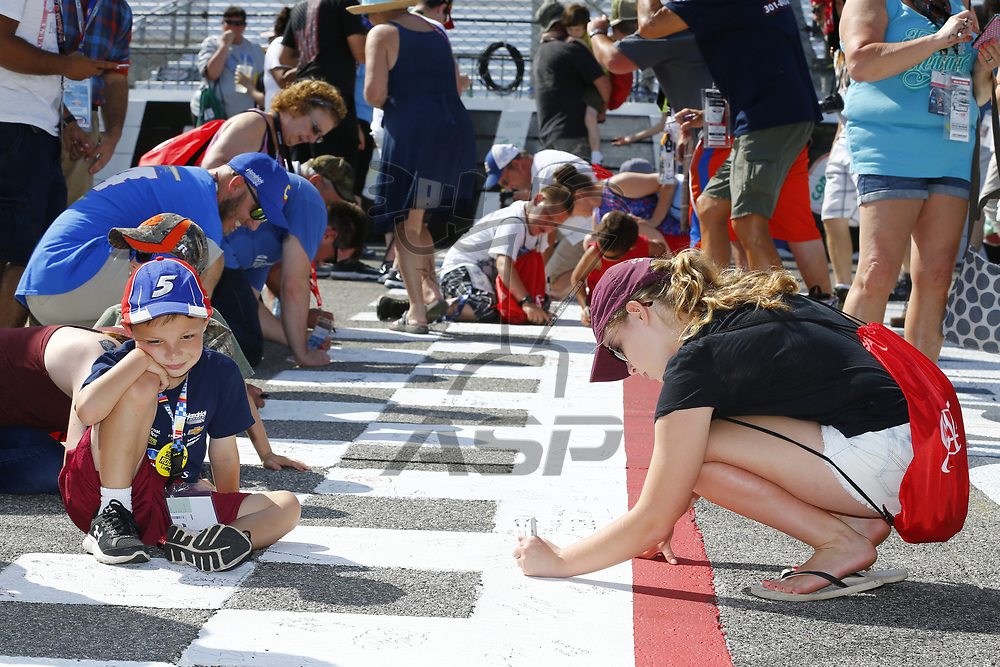 """April 30, 2017 - Richmond, Virginia, USA: Fans sign the start-finish line during the """"Track Takeover"""" prior to the start of the Toyota Owners 400 at Richmond International Speedway in Richmond, Virginia."""