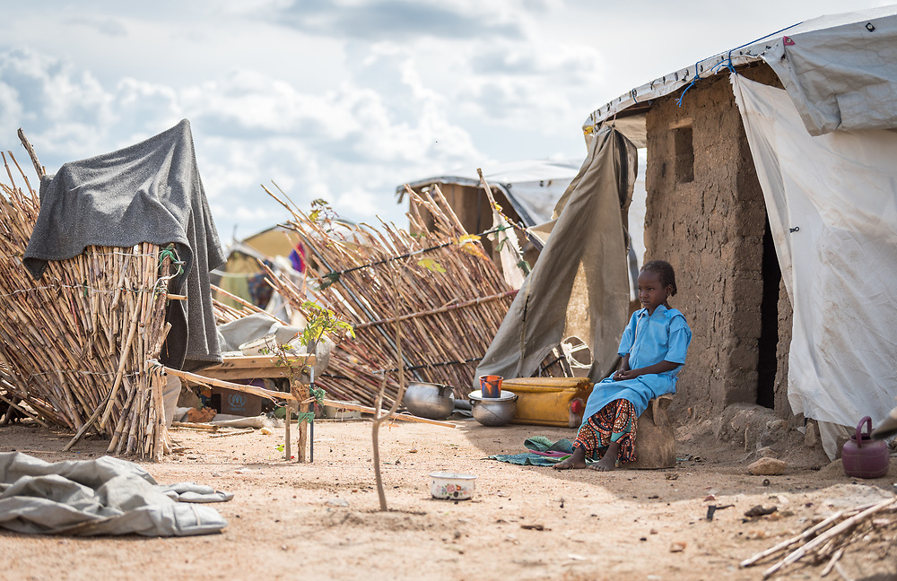 31 May 2019, Mokolo, Cameroon: A girl sits outside her home in Minawao. The Minawao camp for Nigerian refugees, located in the Far North region of Cameroon, hosts some 58,000 refugees from North East Nigeria. The refugees are supported by the Lutheran World Federation, together with a range of partners.