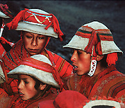 Andean mountain boys dress in traditional red ponchos and felt hats in the Cordillera Urubamba, Andes highlands, Peru, South America. The moderately strenuous trek from Lares to Patacancha (near Ollantaytambo) traverses rugged, little-visited country in the Cordillera Urubamba across passes at 13,800 and 14,200 feet elevation. A five hour bus ride from Cuzco reaches Lares, where you can soak in developed hot spring pools. Llamas and horses carried our loads for two nights of camping at 12,500 feet elevation.