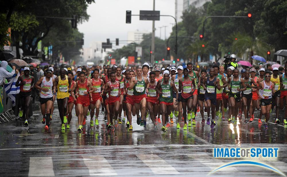 Aug 21, 2016; Rio de Janeiro, Brazil; Runners run in the rain during the marathon during the Rio 2016 Summer Olympic Games at Sambodromo.