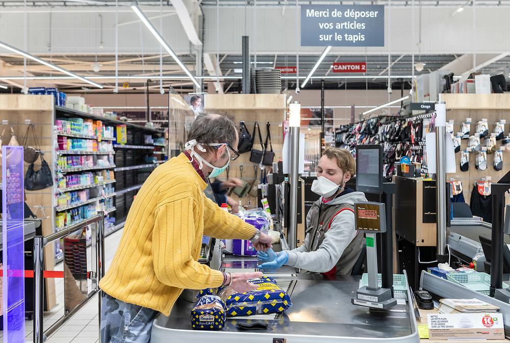 L'Intermarché de La Loupe, le 18 mars 2020<br /> Un client règle le paiement des courses à la caisse du supermarché. Il porte un masque de protection, ainsi que le jeune caissier.