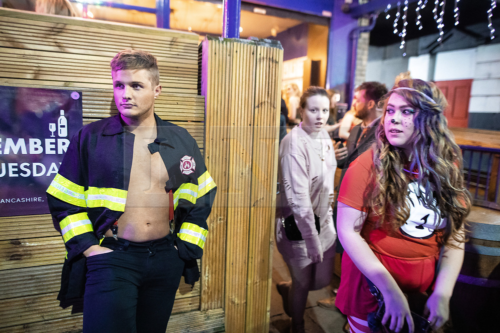 © Licensed to London News Pictures . 26/12/2018. Wigan, UK. A man wearing a fireman's costume waits outside a bar on King Street . Revellers in Wigan enjoy Boxing Day drinks and clubbing in Wigan Wallgate . In recent years a tradition has been established in which people go out wearing fancy-dress costumes on Boxing Day night . Photo credit: Joel Goodman/LNP