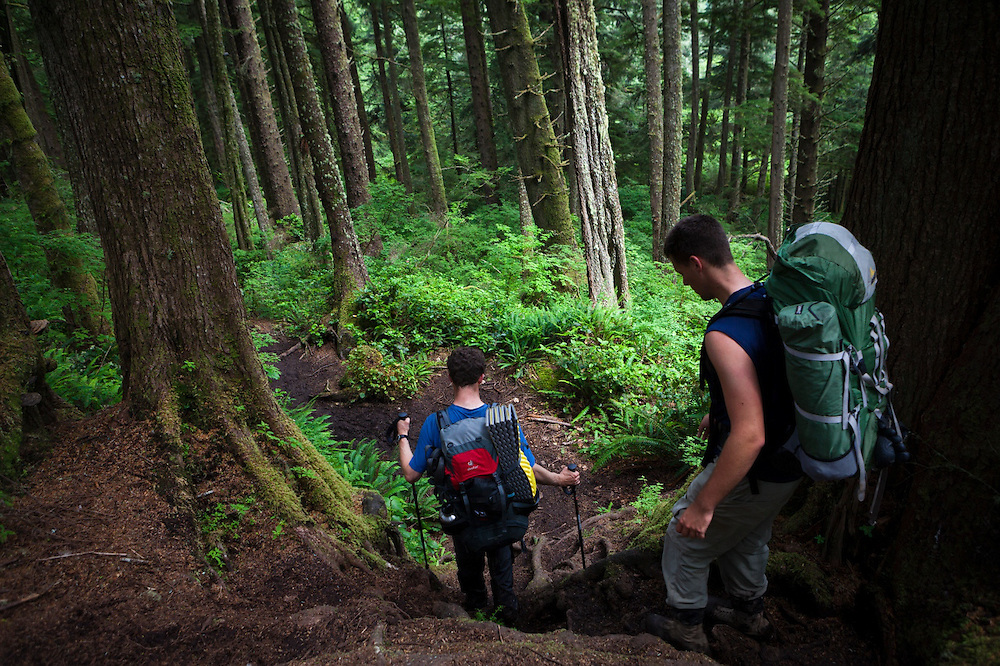 Zach Podell-Eberhardt (left) and Henry hike through dark forest along the West Coast Trail, British Columbia, Canada.
