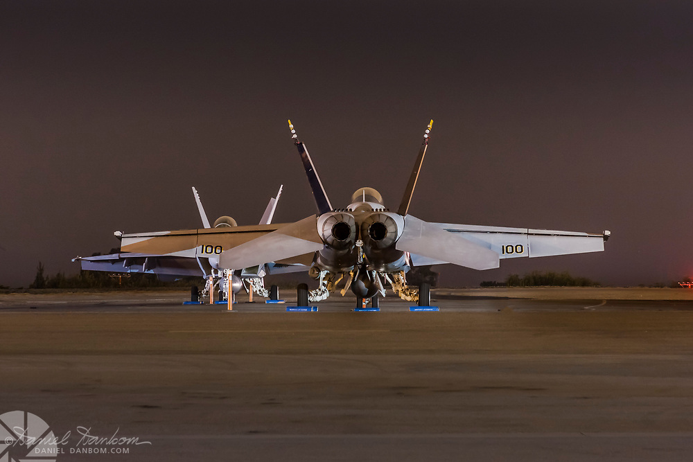 Two F-18s, on the ramp at MYR, Monterey Jet Center, night, rear view.
