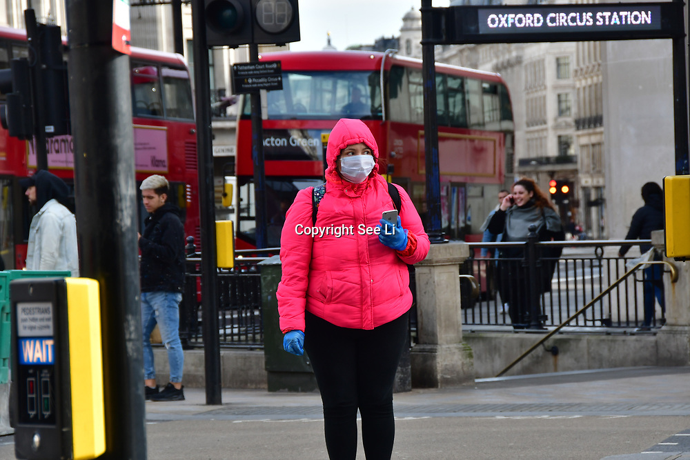 A woman wearing a mask cross the street during Coronavirus - Pandemic hit Oxford Street many shops closure a few open but empty on 21 March 2020, UK.
