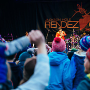 Micahel Franti and Spearhead perform to a packed crowd in Teton Village, Wyoming. Michael Franti on stage photographed through packed crowd.