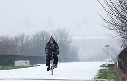 © Licensed to London News Pictures.18_01_2013 LONDON UK.Heavy Snow fall hit in London a brave cyclist on the route to the London Olympic Stadium today, which can be seen faintly in the distance. Photo credit : Andrew Baker/LNP