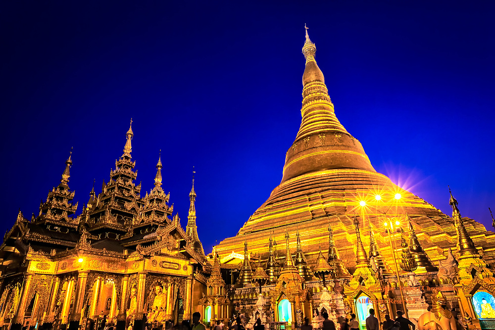 Dragon Dusk:  Dusk and the spectacular sight of the gold plated Great Shwedagon Pagoda with a domineering Stupa and its diamond encrusted top, Yangon Myanmar.