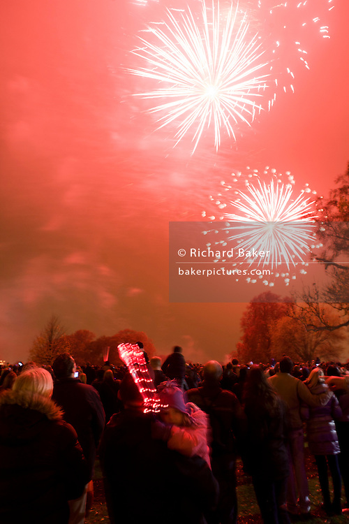 Young child turns away from loud bangs during a 5th November fireworks event in a public south London park.