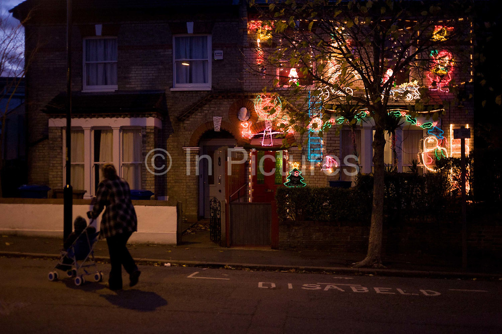 Mother and child pass a residential house adorned with a mass of wasteful Christmas lights, the only one in this south London street. Pushing her child in the family pushchair (buggy) the woman crosses the road and looks across to the colours that shine from the otherwise dark street.