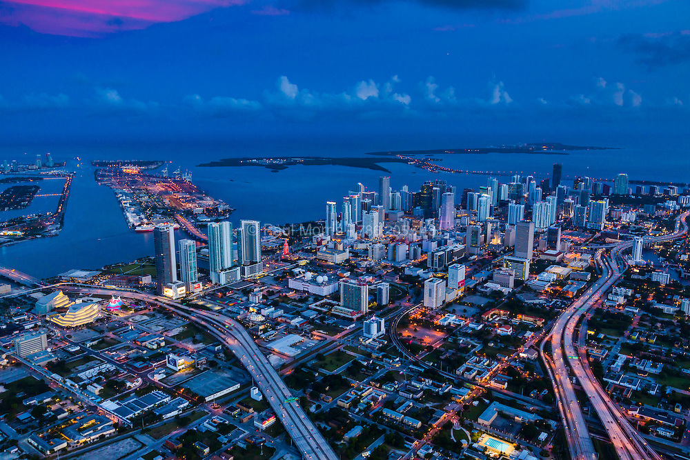 Miami Skyline at twilight with city lights, view looking from northwest to southeast with Biscayne Bay and ocean in the background