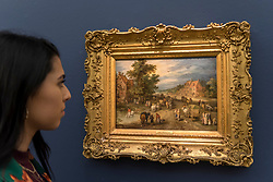"© Licensed to London News Pictures. 29/06/2018. LONDON, UK. A staff member views ""A Village street with carts, villagers and gentlefolk"" by Jan Brueghel the Elder (Est. £2.5-3.5m).  Preview of Old Masters, British, Treasures, Sculptures and Ancient works at Sotheby's New Bond Street to be offered for sale on 3 and 4 July 2018.  Photo credit: Stephen Chung/LNP"
