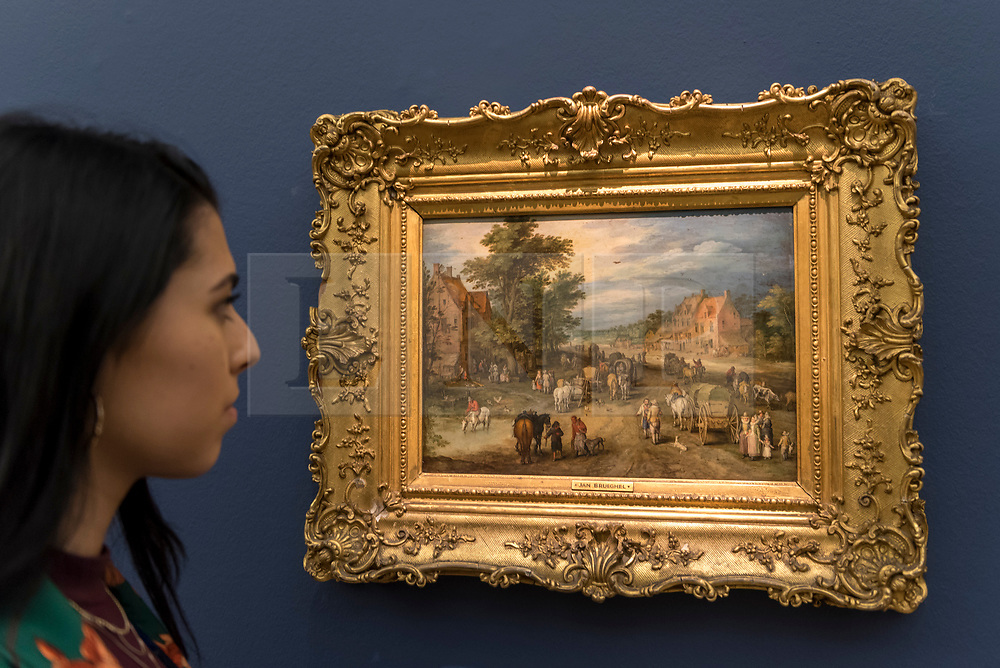 """© Licensed to London News Pictures. 29/06/2018. LONDON, UK. A staff member views """"A Village street with carts, villagers and gentlefolk"""" by Jan Brueghel the Elder (Est. £2.5-3.5m).  Preview of Old Masters, British, Treasures, Sculptures and Ancient works at Sotheby's New Bond Street to be offered for sale on 3 and 4 July 2018.  Photo credit: Stephen Chung/LNP"""