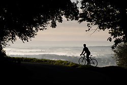 © Licensed to London News Pictures. 23/09/2016. Dorking, UK.  A cyclist stops to view the sunrise over Surrey from Box Hill on the second day of Autumn. Photo credit: Peter Macdiarmid/LNP