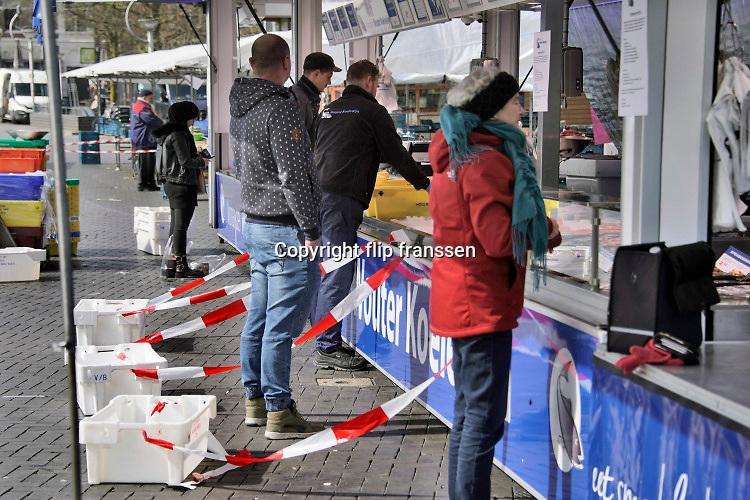 Nederland, Nijmegen, 30-3-2020 In de binnenstad van Nijmegen is het markt. Die is open, maar er zijn maar weinig klanten en ook veel marktkooplui zijn niet gekomen. Sommigen hebben voor hun kraam, marktkraam, vakken gemaakt van afzetlint of bakken geplaatst om de bezoekers te dwingen afstand van 1,5 ,anderhalve, meter te houden . Foto Flip Franssen