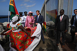 Prince Harry is greeted by Governor General Dame Cecile la Grenade (in pink) and watches a dancer perform as he arrives at the Grenada Cruise Port in Grenada, during the second leg of his Caribbean tour.