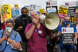 Staff nurse David Carr addresses NHS staff marching from St Thomas' Hospital to Downing Street to protest against the NHS Pay Review Body's recommendation of a 3% pay rise for NHS staff in England on 30th July 2021 in London, United Kingdom. The protest march was supported by Unite the union, which has called on incoming NHS England Chief Executive Amanda Pritchard to ensure that a NHS pay rise comes from new Treasury funds rather than existing NHS budgets and which is shortly expected to put a consultative ballot for industrial action to its members.