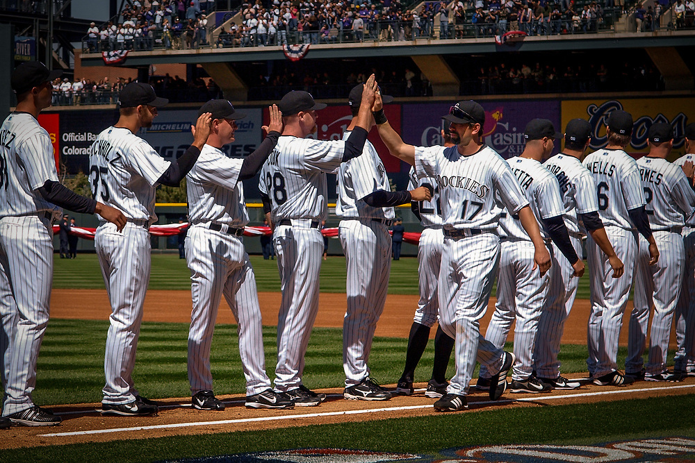 Colorado Rockies players greet TODD HELTON with high fives.