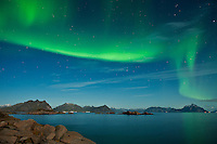 Northern Lights fill sky above mountains of Lofoten Islands, Norway