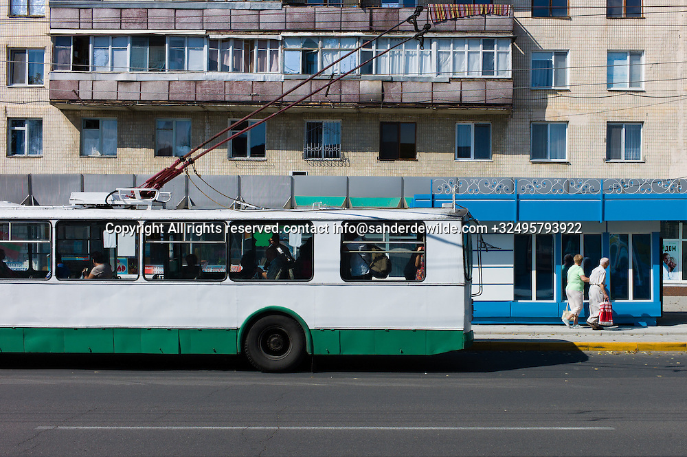 20150825  Moldova, Transnistria, Tiraspol.A typical street scene in Tiraspol where a trolley bus leaves at the bus station in the central street called 25th October Street with typical appartments and colors.