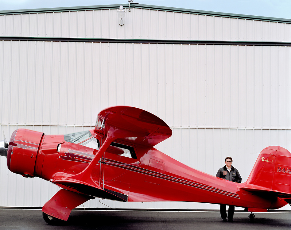Pilot standing next to Beechcraft Staggerwing Model 17 aircraft in front of airplane hangar. Spokane, WA