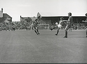 League of Ireland vs Liverpool FC.    (M87)..1979..18.08.1979..08.18.1979..18th August !979..In a pre season friendly the League of Ireland took on Liverpool FC at Dalymount Park Phibsborough,Dublin. The league team was made up of a selection of players from several League of Ireland clubs and was captained by the legendary John Giles. Liverpool won the game by 2 goals to nil..The scorers were Hansen and McDermott...Image shows Terry McDermott firing a shot at the Irish goal as John Giles attempts a block.