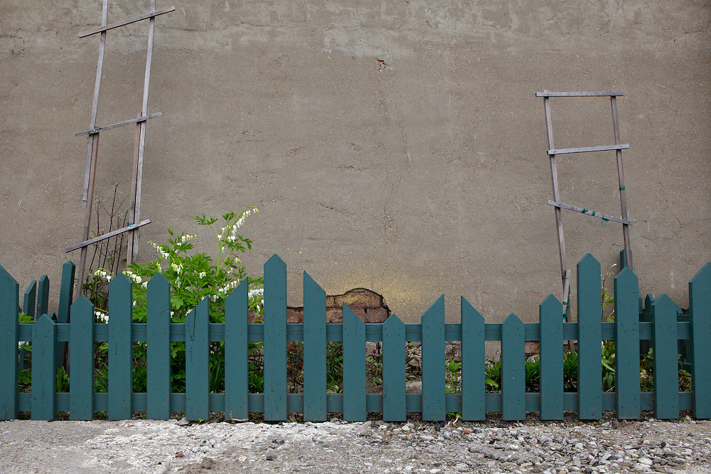 A small strip beside the wall in the parking lot by McWood Studios converted into a fenced off garden.