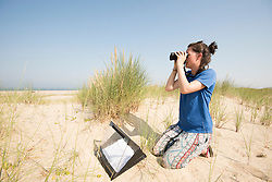 Project Officer Emma Witcutt observing colony, Little tern Sternula albifrons monitoring site, part of an EU Life Project to protect this species, Winterton-on-Sea, Norfolk, July